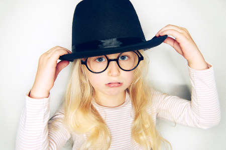 Cute little girl with long blonde hair wearing glasses and holding the rim of her black hat looking sulky against a white background