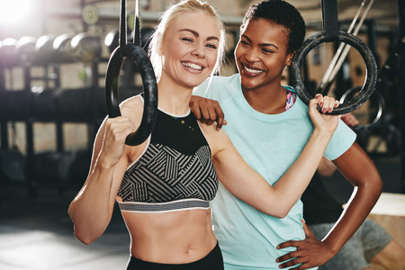 Two smiling young female friends in sportswear standing together by rings in a gym before a workout