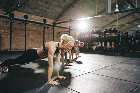 Diverse group of fit people in sportswear doing pushups together on a gym floor during a workout session Reklamní fotografie