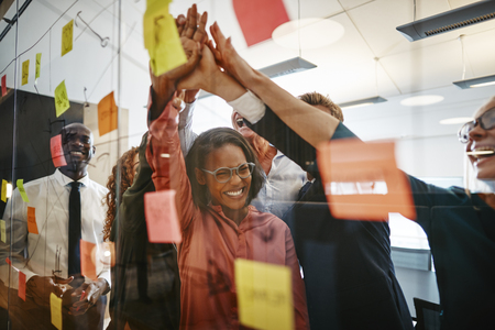 Excited group of diverse businesspeople celebrating with high fives after a brainstorming session with sticky notes in an office 版權商用圖片