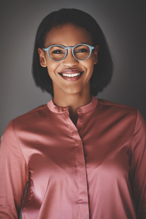 Smiling young African business professional wearing glasses and smiling confidently while standing against a gray background Banco de Imagens