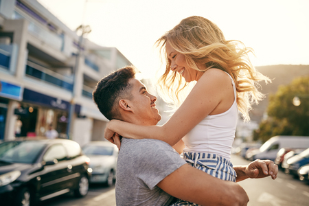 Smiling young man holding his girlfriend in his arms while having a good time together in the city Stock Photo