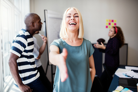 Laughing young female designer extending a welcoming handshake while standing in a bright modern office with colleagues talking in the background Stock Photo