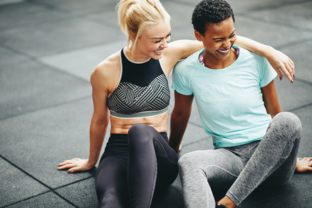 Two laughing young female friends in sportswear resting together on the floor of a gym after a workout