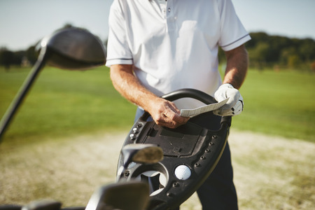 Sporty senior man reading his scorecard while standing on a fairway playing golf on a sunny day
