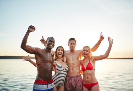 Unbeschwerte Gruppe lachender junger Freunde, die Arm in Arm zusammenstehen und am späten Nachmittag Spaß an einem See haben lake