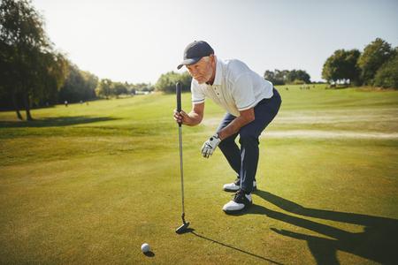 Uomo anziano sportivo accovacciato su un verde che pianifica il suo putt mentre si gode una partita di golf in una giornata di sole