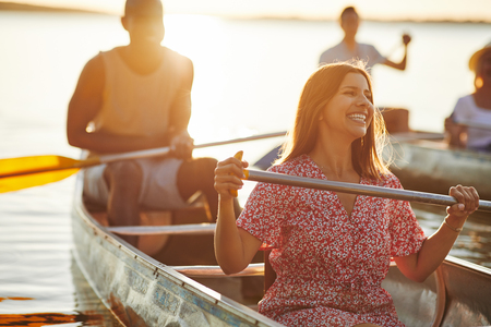 Young woman laughing while paddling a canoe with her boyfriend and another couple on a sunny afternoon in the summer Stock Photo