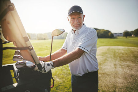 Smiling senior man standing by a golf cart looking out at the fairway while enjoying a round of golf on a sunny day