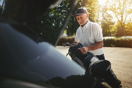 Smiling senior man packing his golf bag into the trunk of his car after playing a round of golf on a sunny afternoon Foto de archivo