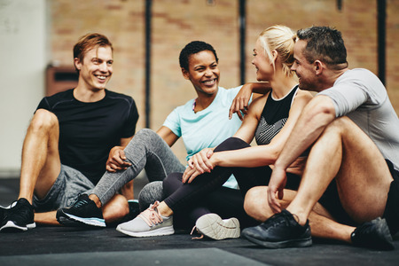 Smiling group of fit people in sportswear laughing together while sitting on the floor of a gym after a workout Banco de Imagens