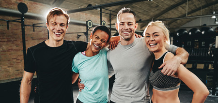 Laughing group of diverse friends in sportswear standing arm in arm after working out together at the gym Stockfoto