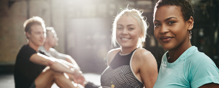 Two smiling young women in sportswear sitting together on the floor of a gym after a workout with two male friends