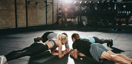 Group of fit young people in sportswear planking together on the floor of a gym during an exercise class