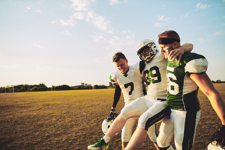 American football players carrying an injured teammate off the field during a practice session in the late afternoon Stockfoto
