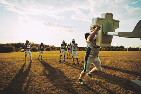 Team of young American football players tackling sleds during a practice session together on a sports field Stock Photo