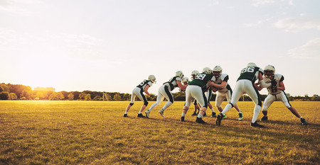 Group of young American football players doing defensive drills on a sports field during an afternoon practice session Reklamní fotografie - 118921724