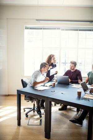 Diverse Gruppe fokussierter junger Designer, die gemeinsam an einem Projekt arbeiten, während sie in einem Büro um einen Sitzungstisch sitzen