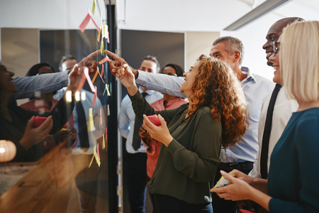 Young businesswoman and her diverse team laughing together while brainstorming with sticky notes on a glass wall in a modern office Фото со стока
