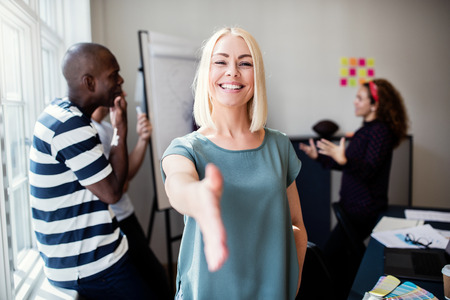 Smiling young female designer extending a welcoming handshake while standing in a bright modern office with colleagues talking in the background