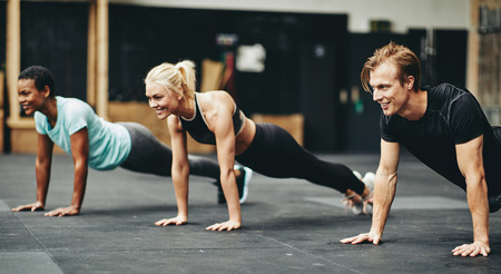 Diverse group of smiling young people in sportswear doing pushups together on a gym floor during a workout session Stok Fotoğraf