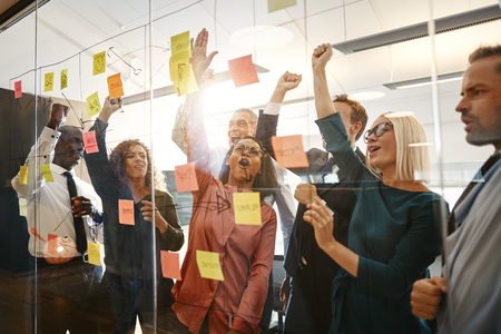 Ecstatic group of diverse businesspeople cheering and celebrating together after a brainstorming session with sticky notes in an office