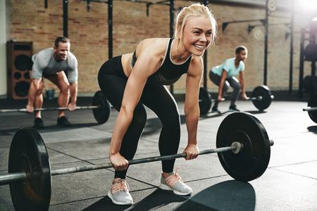 Fit junge Frau in Sportkleidung lächelt, während sie sich darauf vorbereitet, Gewichte während einer Gewichthebersitzung im Fitnessstudio zu heben
