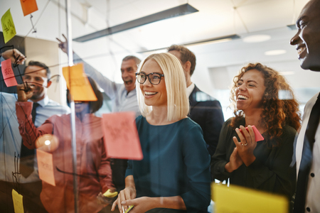 Smiling young businesswoman and her diverse team brainstorming ideas with sticky notes on a glass wall while working together in a modern office
