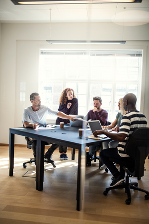 Focused group of young designers discussing paperwork together while sitting around a boardroom table in an office Banque d'images
