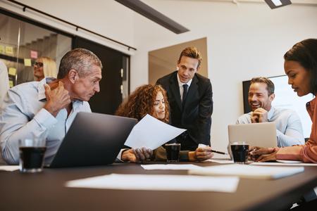 Groep diverse zakenmensen die papierwerk bespreken terwijl ze samen een vergadering hebben in de bestuurskamer van een kantoor Stockfoto