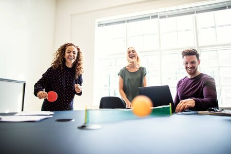 Laughing group of young designers playing table tennis on a boardroom table during a break from work in an office