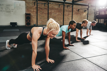 Smiling young woman in sportswear doing pushups at the gym with a group of friends during an exercise class