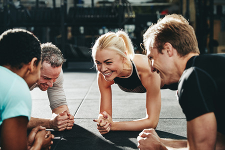 Diverse group of smiling friends in sportswear planking together on a gym floor during a workout session