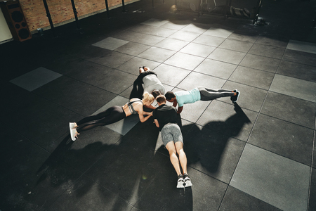 High angle of a fit group of diverse people in sportswear planking together on the floor of a gym during an exercise class