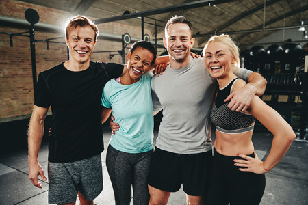 Laughing group of diverse friends in sportswear standing arm in arm after working out together at the gym Stock fotó - 120417163