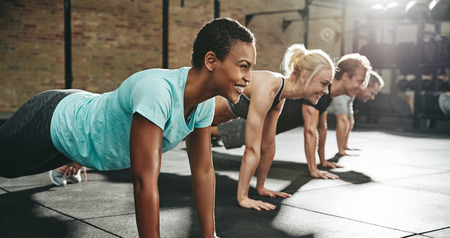 Smiling young African American woman in sportswear doing pushups during an exercise class with a group of friends at the gym Stok Fotoğraf