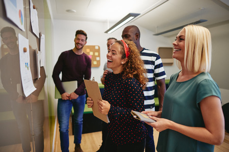 Diverse group of colleagues laughing while reading charts and graphs taped to a wall during a meeting together in a modern office
