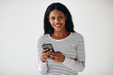 Young African American female entrepreneur smiling and reading a text message while standing against a white background Reklamní fotografie