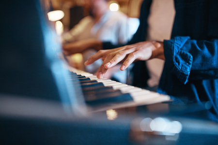 Closeup of an African American musician playing the keyboards during a session in a recording studio