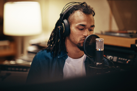 Young African American singer wearing headphones sitting in a recording studio preparing to lay down tracks