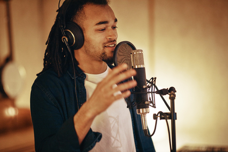 Young African American musician singing into microphone while working on songs during a recording studio session