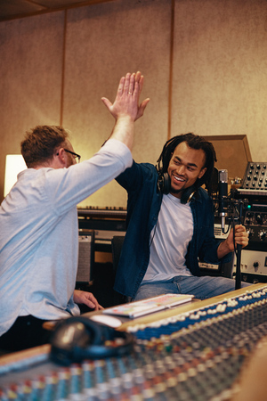 Ecstatic young African American singer high fiving with his music producer after a session in a recording studio