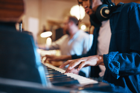Closeup of a young African American musician playing keyboards in a recording studio with a producer in the background