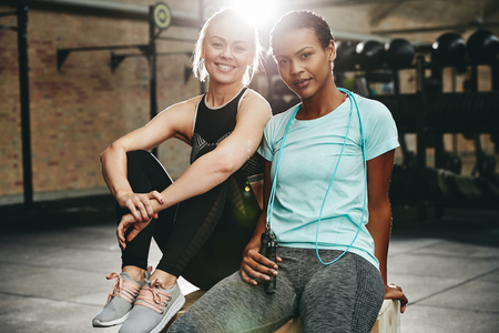 Two smiling young women in sportswear sitting on a box at the gym after an exercise session together Banco de Imagens