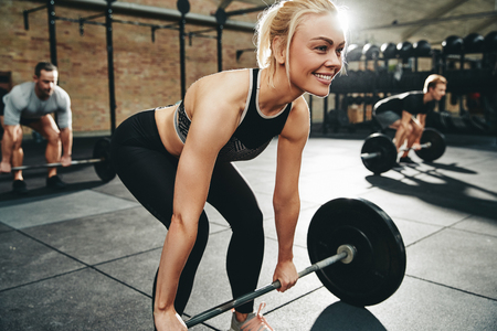 Smiling young woman in sportswear preparing to lift barbells during a weightlifting class in a gym