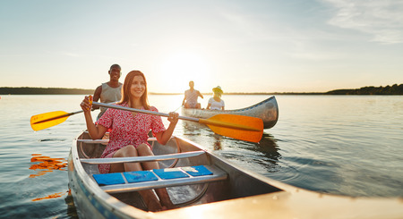 Smiling young woman and her boyfriend enjoying a day canoeing with friends on a lake on a late summer afternoon Stock Photo