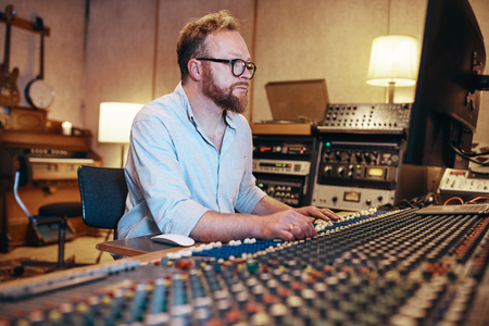 Mature music producer making adjustments on his soundboard while working in a recording studio Stock Photo - 121104608