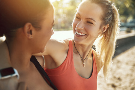 Two laughing young women in sportswear standing arm in arm together outside on a sunny day before a run together
