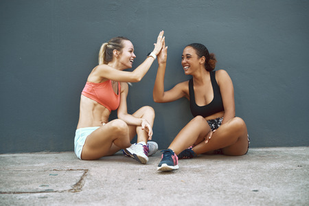 Two fit young women in sportswear sitting on the ground outside laughing and high fiving after working out together