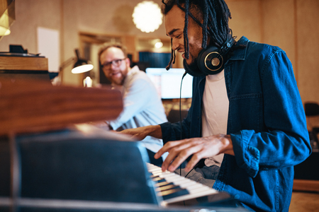 Smiling young African American musician playing keyboards during a recording studio session with a producer in the background